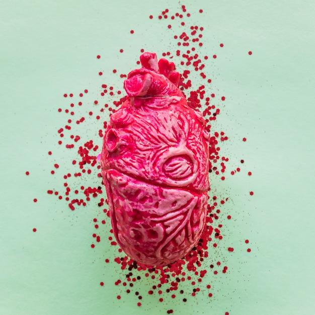 Cuore umano in ceramica rosa con lustrini sul tavolo Foto Gratuite