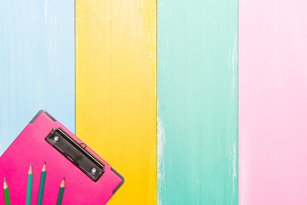 Pink clipboard top view on colorful backgrounds Premium Photo