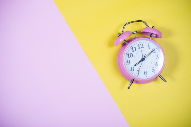 Pink clock on the colorful background, education concept Free Photo