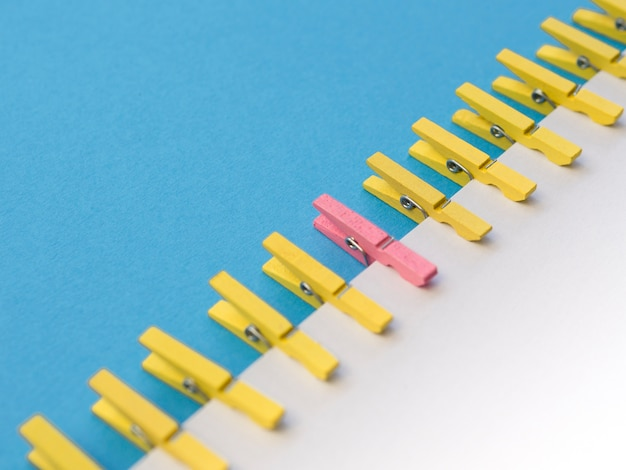 Pink clothespin surrounded by yellow ones Free Photo