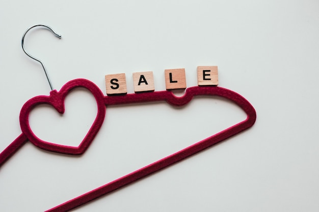 Pink clothing hanger on the white background with the word sale. Premium Photo