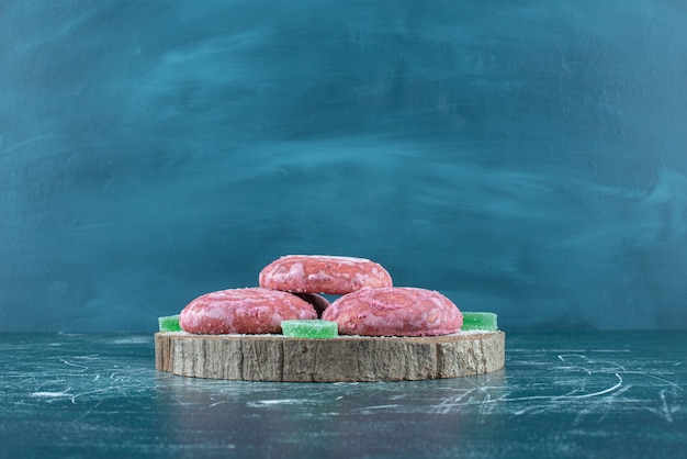 Biscotti e marmellate rivestiti rosa su una tavola di legno sul blu. Foto Gratuite