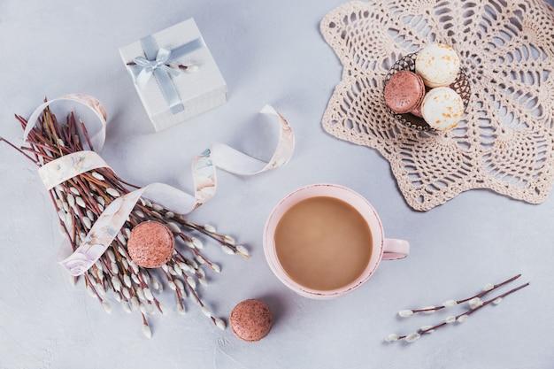 Pink coffee mug with sweet pastel french macaroons Premium Photo
