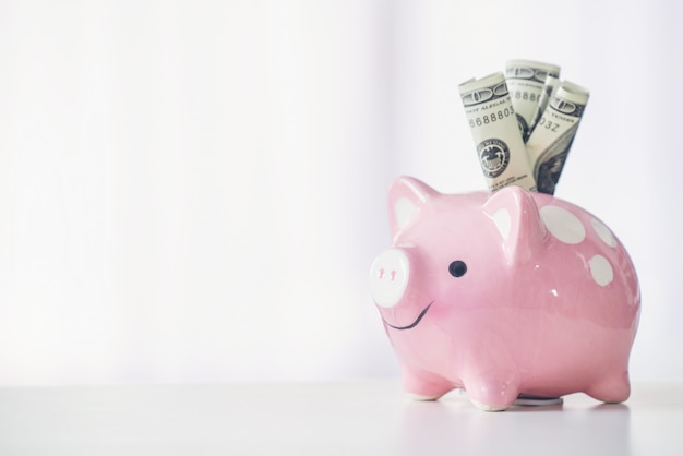 Pink color piggy bank on white table Premium Photo