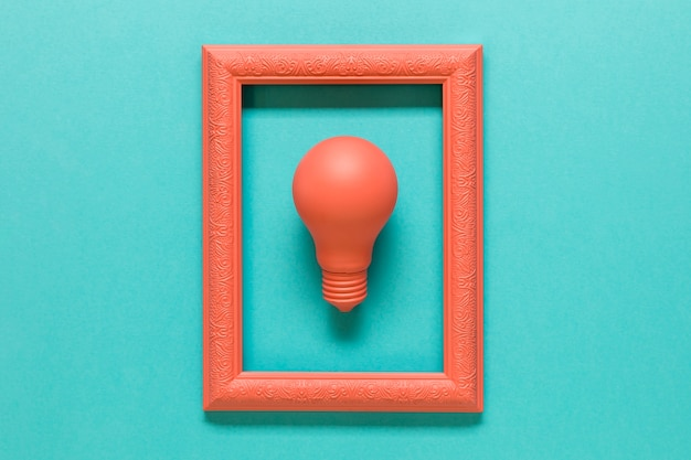 Pink composition with lamp in frame on blue surface Free Photo