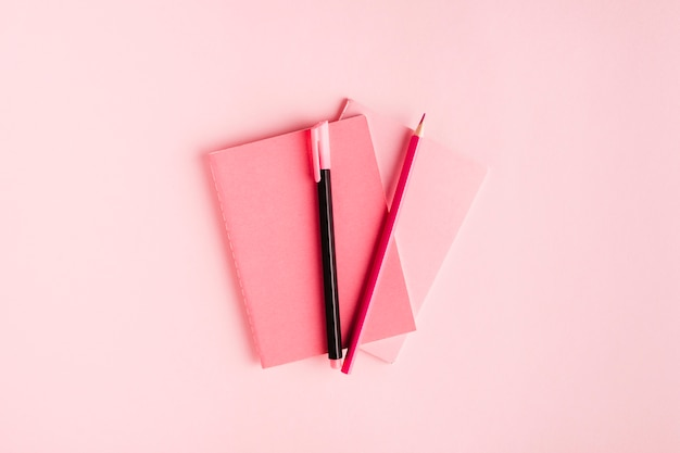Pink composition with notebook and stationery on desk Free Photo