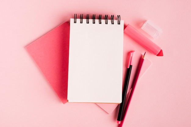 Pink composition with notepad and office supplies on colored surface Free Photo