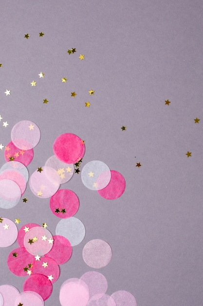 Pink confetti with gold stars on gray   with copyspace Premium Photo