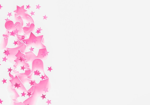 Pink cookie cutter and star confetti christmas festive minimalist border with copyspace Premium Photo