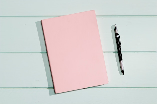 Pink cover of a notepad with pen Free Photo
