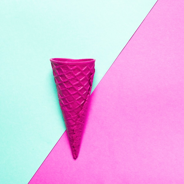 Pink crispy ice cream cone on colorful background Free Photo