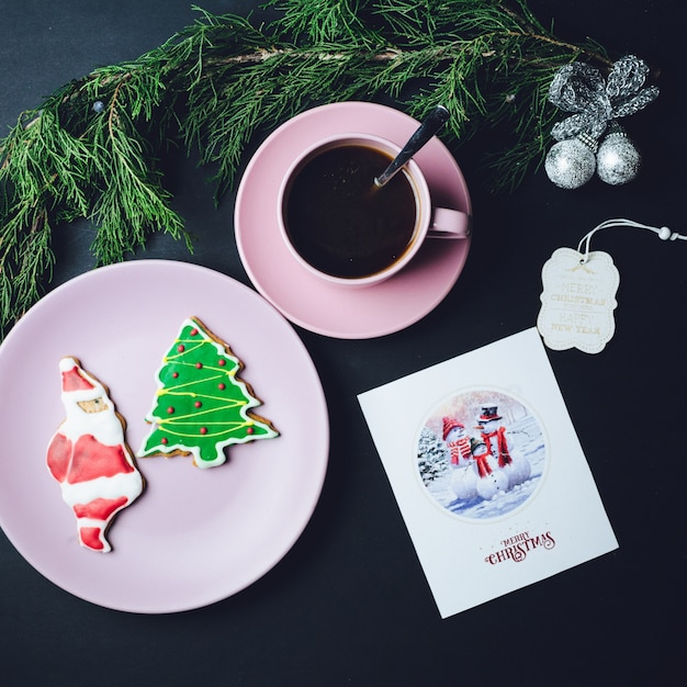 Pink cup of coffee plate with christmas gingerbreads and postcard lie on black table 1304 5669