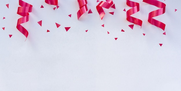 Pink curly ribbons and confetti Premium Photo