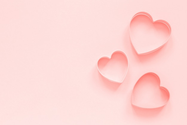 Pink cutters cookies in heart shape on pastel pink background, colar toned. love romantic pattern Premium Photo