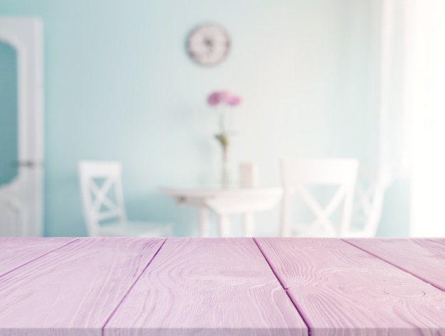Pink desk in the foreground with blur dining table in the background Free Photo