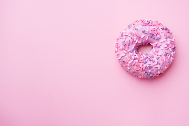 Pink doughnut on pink. top view flat lay. background with copyspace Premium Photo