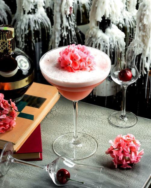 Pink drink with foam in a glass and pink flowers on it Free Photo
