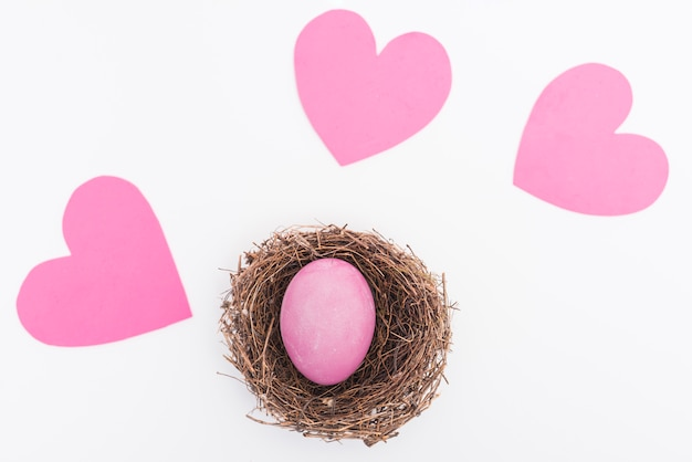 Pink easter egg in nest on table Free Photo