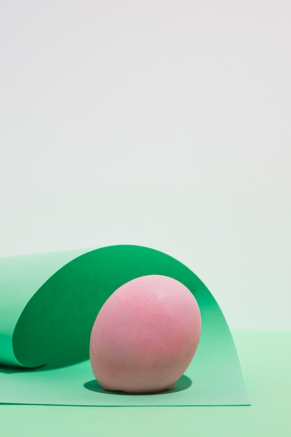 Pink easter egg with paper sheet on light table Free Photo