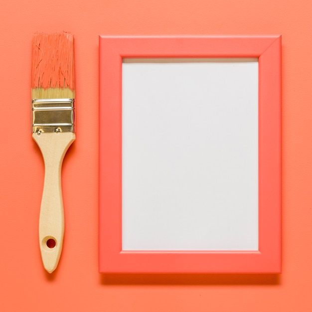 Pink empty frame with brush on colored surface Free Photo