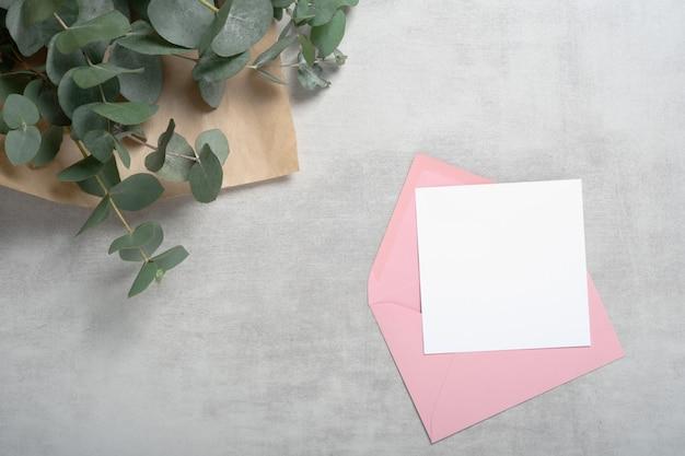 분홍색 봉투 광장 초대 카드, 인사말 카드는 유칼립투스 꽃다발을 모의합니다. 프리미엄 사진