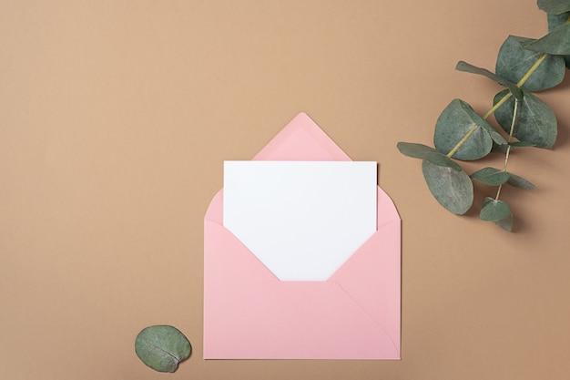 유칼립투스 분기와 핑크 봉투 광장 초대 카드 모형. 복사 공간, 파스텔 베이지 색 배경으로 상위 뷰. 브랜딩 및 광고용 템플릿 프리미엄 사진