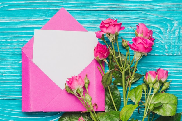 Pink envelope with blank note and floral decoration Free Photo