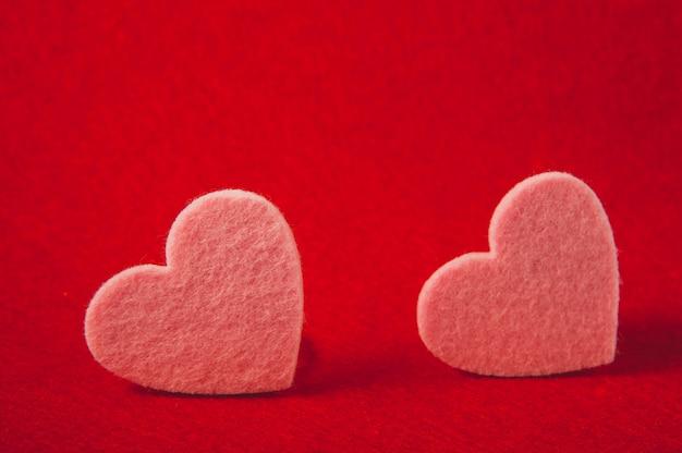 Pink felt hearts on red background, valentine's day Premium Photo