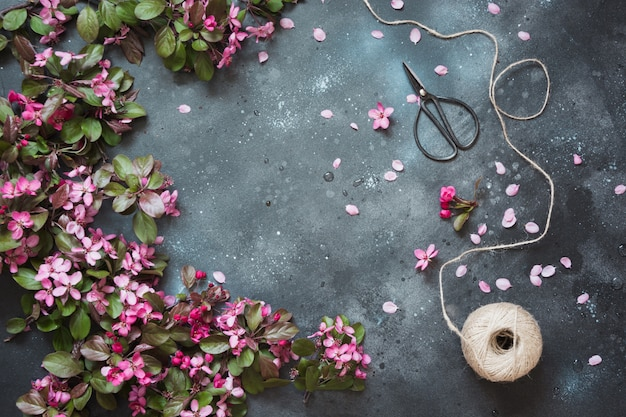 Pink flowers of blossoming fruit tree with accessories for floristics on vintage table. . Premium Photo
