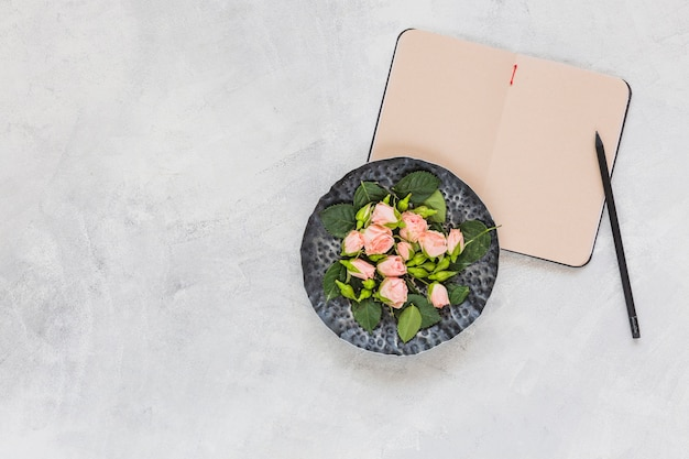 Pink flowers on circular tray with diary and pencil on concrete background Free Photo
