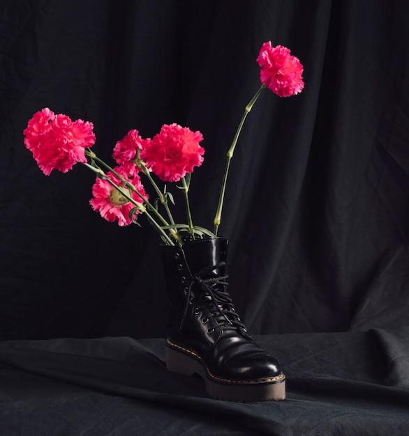 Pink flowers in dark boot Free Photo