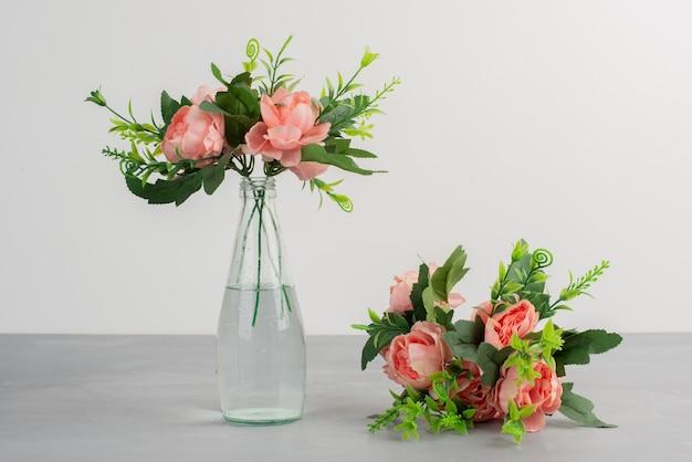 ガラスの花瓶のピンクの花と灰色のテーブルの花の花束 無料写真