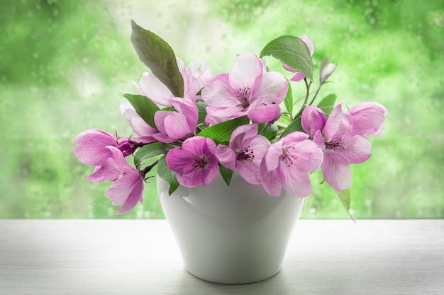 창턱에 작은 흰색 꽃병에 장식 사과 나무의 핑크 꽃. 디자인 엽서, 달력, 책 표지 이미지. 클로즈업, 선택적 포커스. 프리미엄 사진
