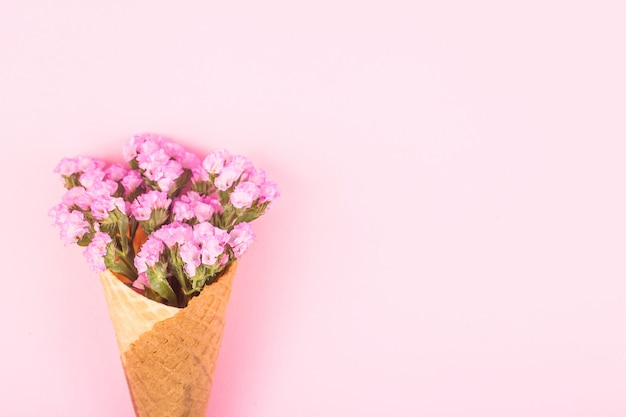 Pink flowers in a waffle cone for ice cream on a pink background. Premium Photo