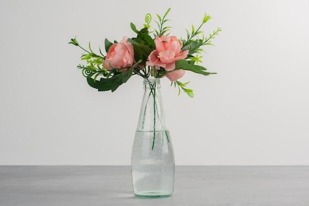 Fiori rosa con foglie verdi in un vaso di vetro Foto Gratuite