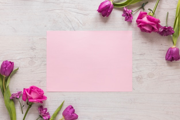 Pink flowers with paper on wooden table Free Photo