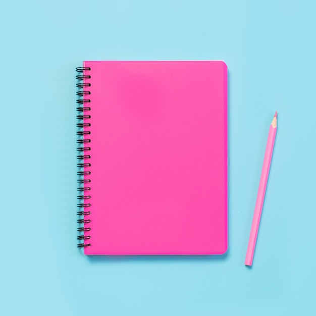 Pink girlish school supplies, notebooks and pens on punchy blue. top view, flat lay. copy space. Premium Photo