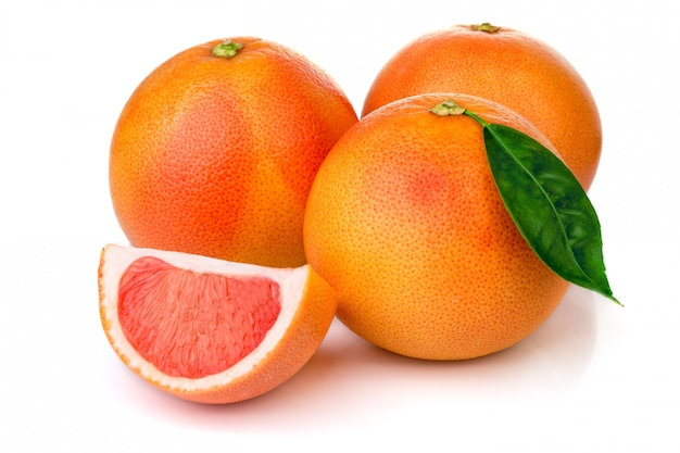 Pink grapefruits with green leaves isolated on white Premium Photo