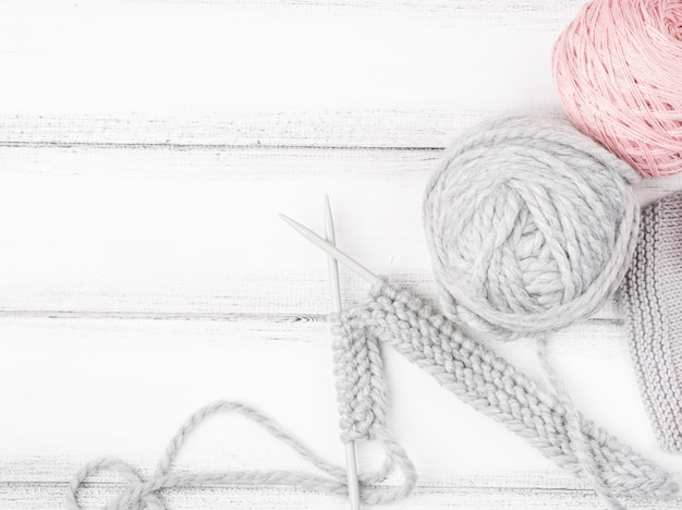 Pink and gray yarn on wood background Free Photo