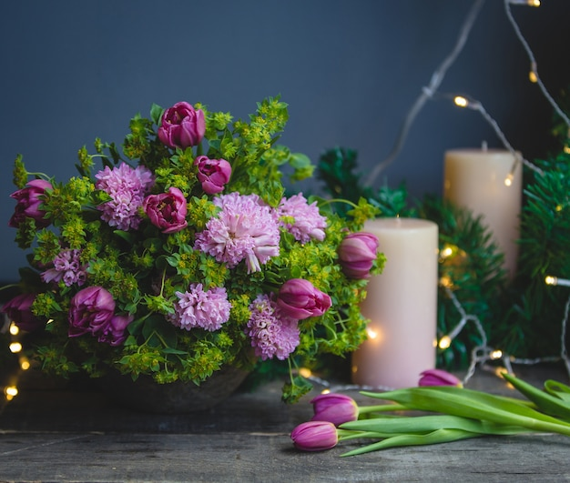 Pink green bouquet, tulips and candles with christmas lights around Free Photo
