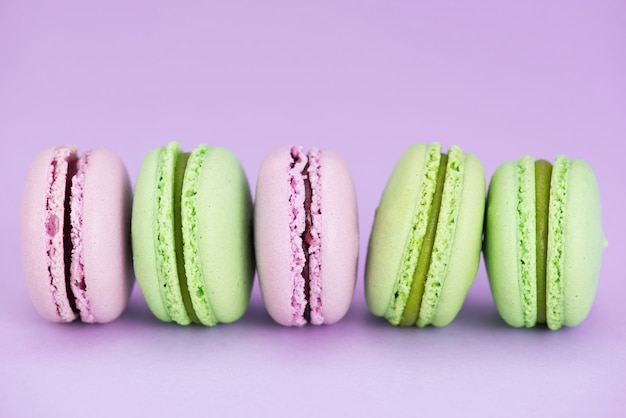 Pink and green macarons in the row Premium Photo