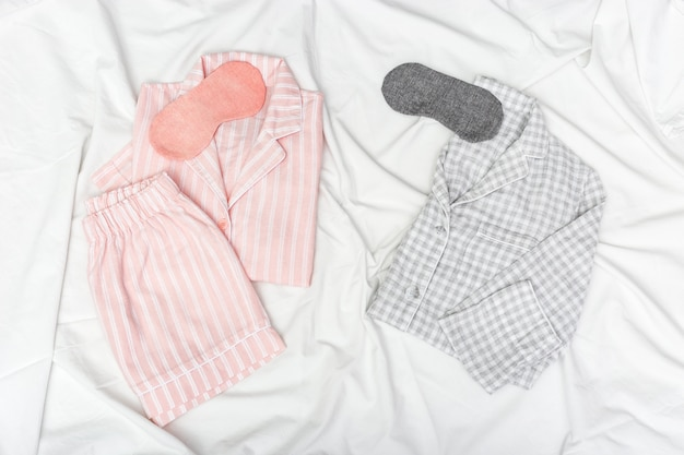 Pink and grey pajamas for two people, and sleep mask for eye on white cotton bedsheet. Premium Photo