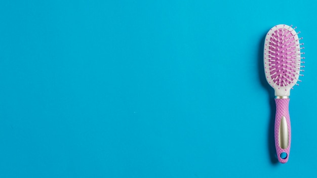 Pink hair brush on blue background Free Photo