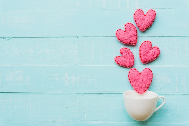 Pink heart on blue and white color wooden background Premium Photo