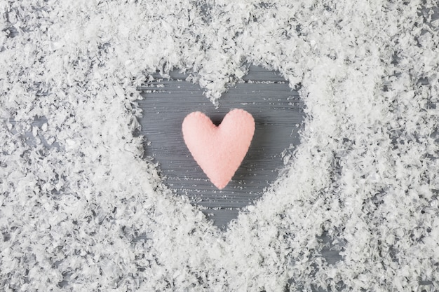 Pink heart between decorative snow on wooden desk Free Photo