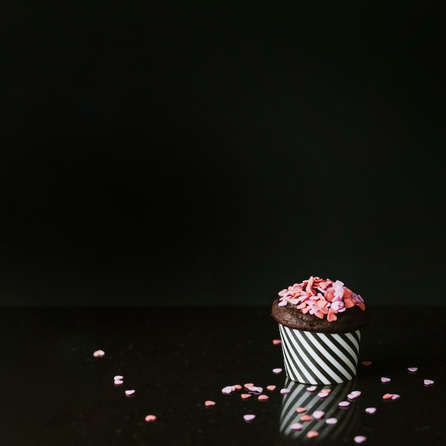 Pink heart shape sprinkles on cupcake over black background Free Photo