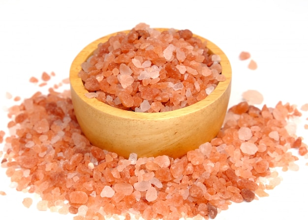 白い背景に分離された木製のボウルにピンクのヒマラヤ塩 Premium写真