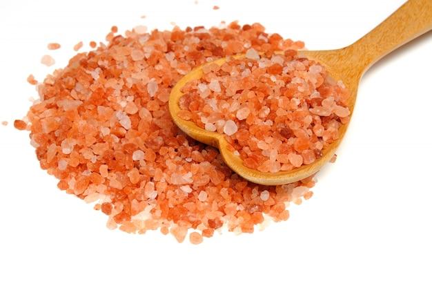 木のスプーンで白い背景で隔離のピンクのヒマラヤ塩 Premium写真