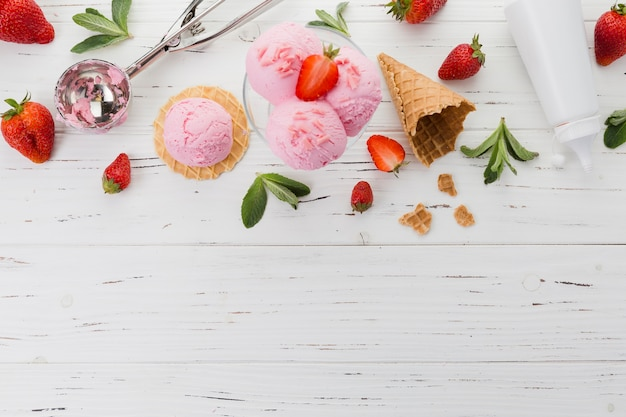 Pink ice cream with strawberries and scooper Free Photo