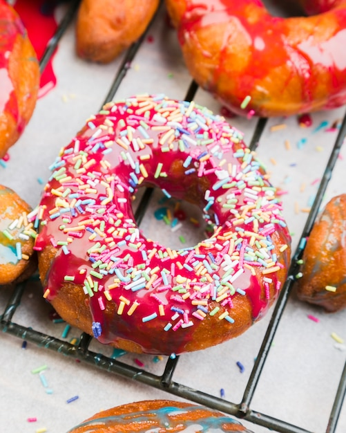 Pink iced doughnut covered in sprinkles on metallic tray
